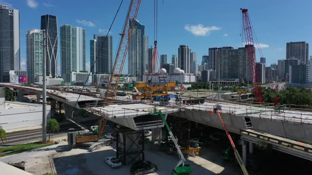 """in an aerial view, construction workers build the """"signature bridge,"""" at i-95 and i-395 that replaces an older bridge on september 27, 2021 in miami,... - bridge built structure stock videos & royalty-free footage"""