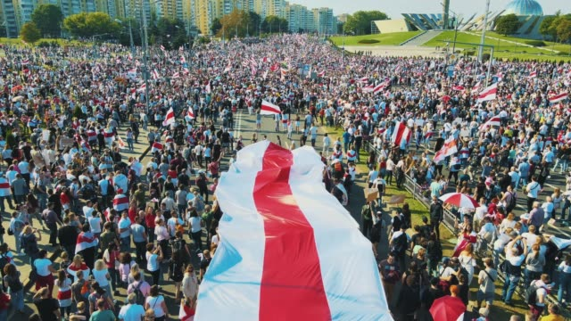 in an aerial view from a drone a mass of protesters gather holding a giant white red white flag of belarus during a demonstration on august 30 2020... - belarus stock videos & royalty-free footage