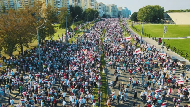 in an aerial view from a drone, a mass of protesters gather holding a giant white - red - white flag of belarus during a demonstration on august 30,... - white点の映像素材/bロール