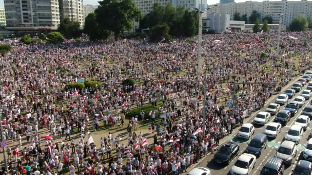 vídeos y material grabado en eventos de stock de in an aerial view from a drone, a mass of tens of thousands of protesters gather during a demonstration as traffic moves on the highway on august 16,... - bielorrusia