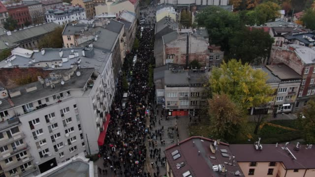 in an aerial view from a drone, crowds move through the streets as they wear protective face masks and hold banners to protest for the fourth day... - polonia video stock e b–roll