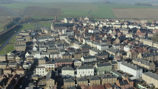 in an aerial view from a drone, little to no traffic or pedestrians move through the streets of poundbury village on january 10, 2021 in poundbury,... - village stock videos & royalty-free footage