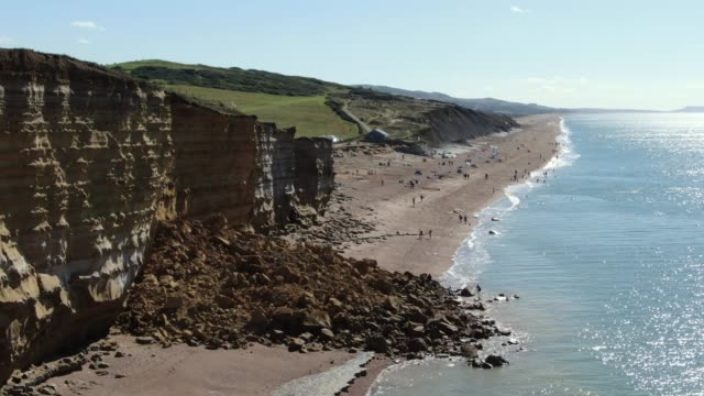 in an aerial view from a drone, rocks are left below a cliff at hive beach after a 9,000 ton cliff fell on august 30, 2020 in burton bradstock,... - land stock videos & royalty-free footage
