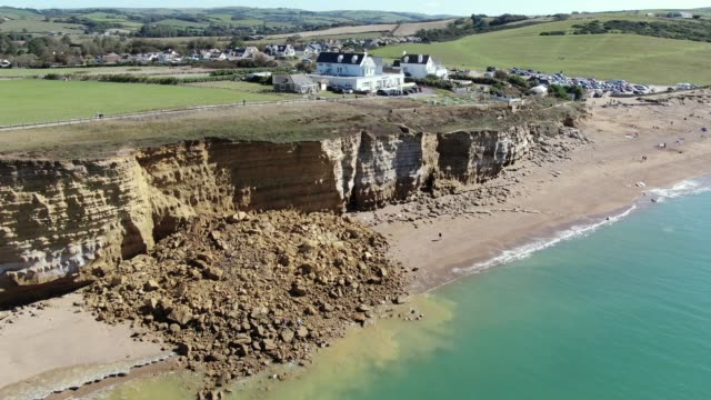 in an aerial view from a drone, rocks are left below a cliff at hive beach after a 9,000 ton cliff fell on august 30, 2020 in burton bradstock,... - coastal feature stock videos & royalty-free footage