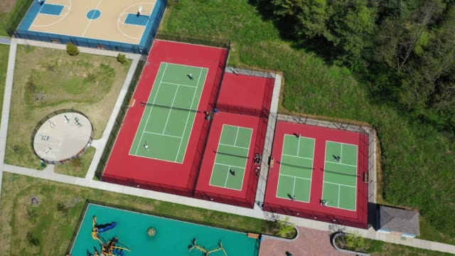 vidéos et rushes de in an aerial view from a drone, tennis players at sweet hollow park observe new york state rules including 'singles' games only on may 17, 2020 in... - en individuel