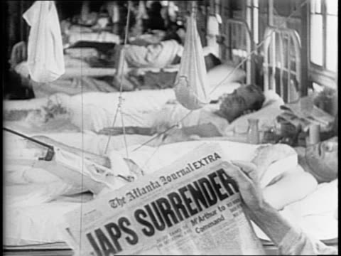In Atlanta inside Lawson General Hospital wounded veteran in hospital bed reading news headline on Japanese surrender / in New York City's China Town...