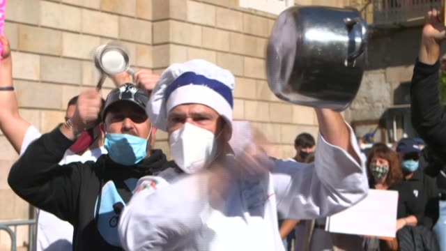 in barcelona, hospitality industry workers take to the streets, banging pots and pans and throwing eggs at the town hall following an order for bars... - cooking pan stock videos & royalty-free footage