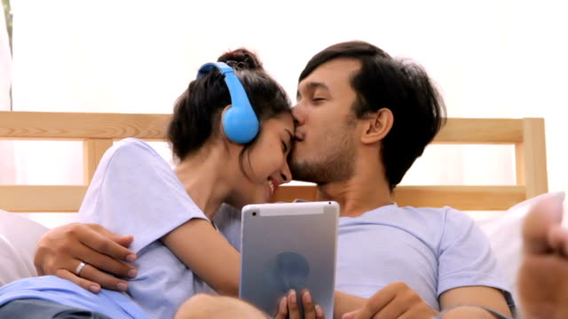 in bed whilst using digital tablet.hd format. - coppia di giovani video stock e b–roll