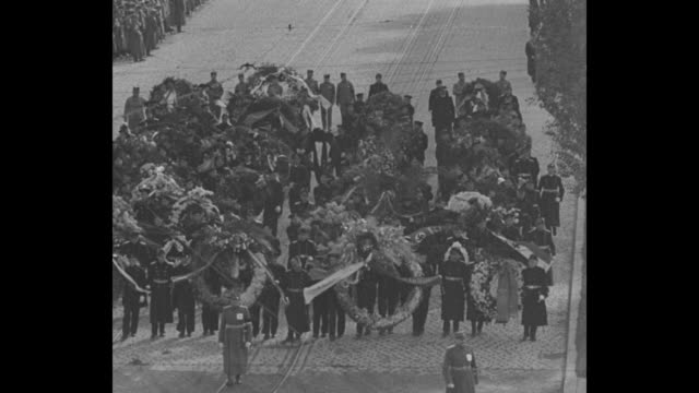 In Belgrade Yugoslavia mourners walk in unison on a broad avenue / people carrying enormous floral arraignments / trucks hauling staggering amount of...