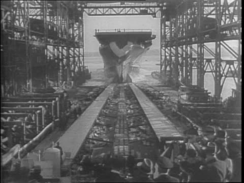 in boston shipyard aircraft carrier uss bunker hill under construction / crowd watches christening of ship and it launches - anno 1942 video stock e b–roll