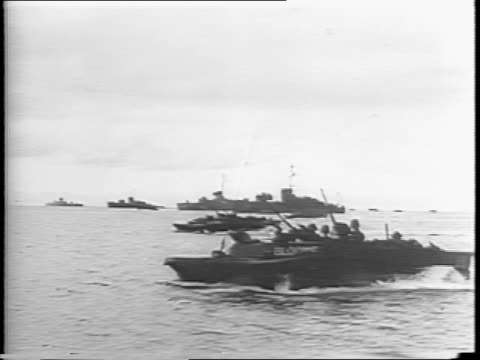 in brunei bay battleships fire on coast / gunners in turrets fire rounds / battleship fires multiple rounds at once / explosions erupt on shore /... - amfibiefordon bildbanksvideor och videomaterial från bakom kulisserna