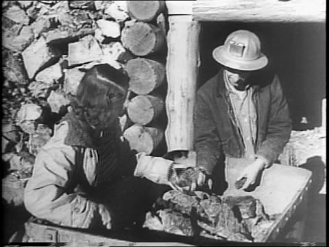 In California's Siskiyou Mountains shots of Dorothea Moroney the Chrome Queen in a tent at her chrome mine / mining cart goes by miners on track /...