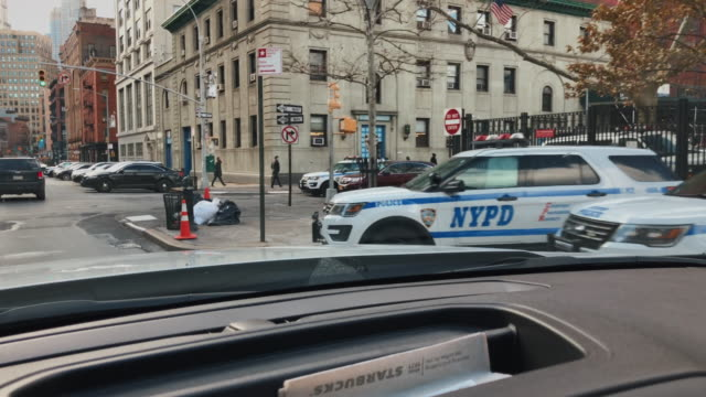 in car camera perspective driving past parked police vehicles in new york city, united states of america - urban sprawl stock videos & royalty-free footage