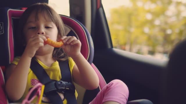 vídeos de stock, filmes e b-roll de em segurança de carro para crianças. uma menina sentada em uma cadeira especial - cadeirinha cadeira