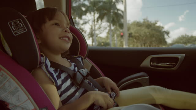 in car safety for children. little girl sitting in a special car seat - vehicle seat stock videos & royalty-free footage