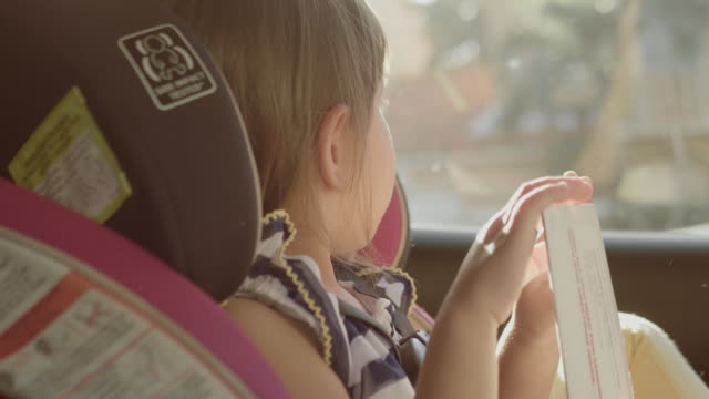vídeos de stock e filmes b-roll de in car safety for children. little girl sitting in a special car seat - cadeira