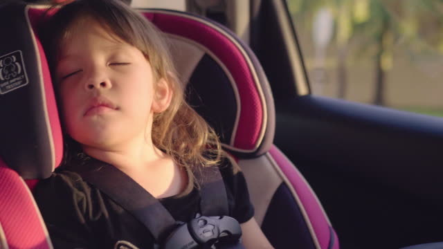 in car safety for children. little girl sitting in a special car seat - travel destinations stock videos & royalty-free footage