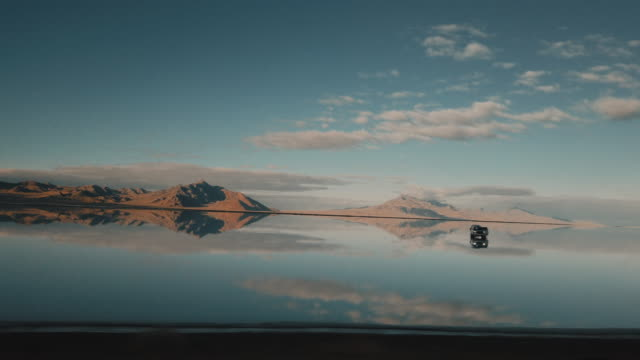stockvideo's en b-roll-footage met in car tracking shot showing a 4x4 parked on the flooded bonneville salt flats, utah, united states of america - bonneville zoutvlakte