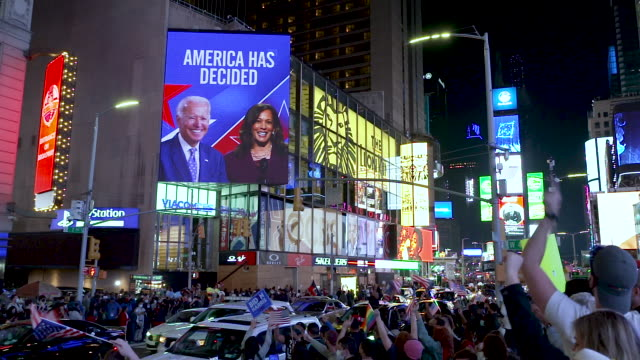 in celebration of the 46th president-elect joe biden and his vice-president kamala harris billboards display their image in midtown manhattan's times... - medium group of people stock-videos und b-roll-filmmaterial