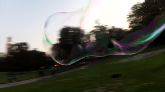 vidéos et rushes de in central park in nyc a man creates giant bubbles that blow across the lawn eight shots - salmini