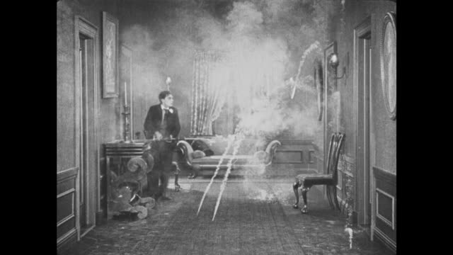 1921 in dark hallway, man (buster keaton) lights candle that turns out to be firework - スラップスティックコメディ点の映像素材/bロール