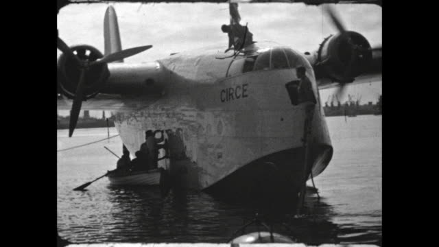 in durban harbor, passengers boarding the short empire flying boat 'circe' from small craft, crew readies the plane for takeoff. - 水上飛行機点の映像素材/bロール