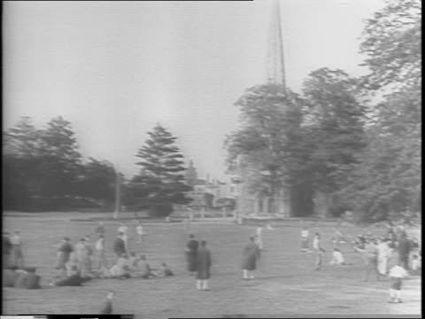 in england / convalescing soldiers play and watch a game of baseball on the green, church in background. - 1943 stock-videos und b-roll-filmmaterial