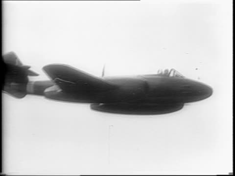 in england / ground crew members polish the gloster meteor as it waits on the tarmac / a ground crewman paints the word 'britannia' on the plane / an... - war stock-videos und b-roll-filmmaterial