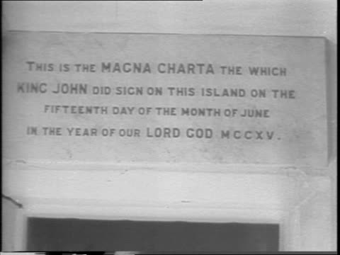 vídeos de stock e filmes b-roll de in england / sign above an ancient copy of the original magna carta / miss frances day, american-born actress and other women page through the... - magna carta documento histórico