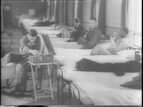 vídeos de stock, filmes e b-roll de in england / soldiers sit on a row of hospital beds laughing with one another as one in a wheelchair puts on a phonograph record / soldier in... - cadeira de rodas equipamento ortopédico