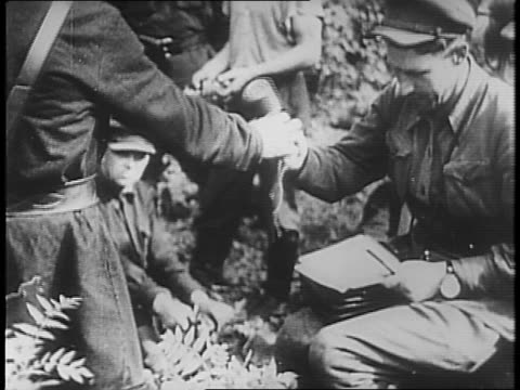 in forest uniformed soldiers instructs peasants on use of hand grenades / pistols and grenades are passed out to peasants / three still photographs... - execution stock videos & royalty-free footage