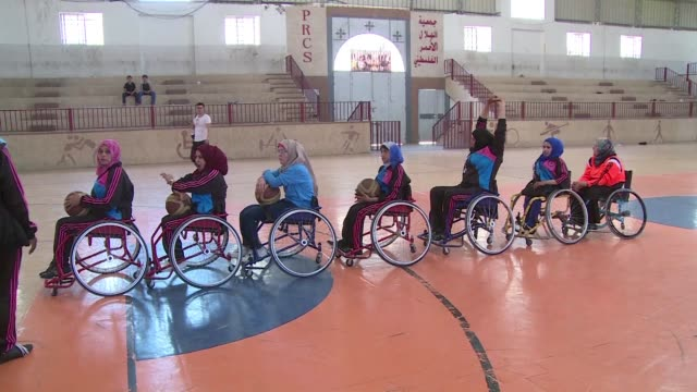 in front of a gyms empty bleachers a group of women in wheelchairs threw passes to one another practicing to form a female paralympic basketball team... - wheelchair basketball stock videos and b-roll footage