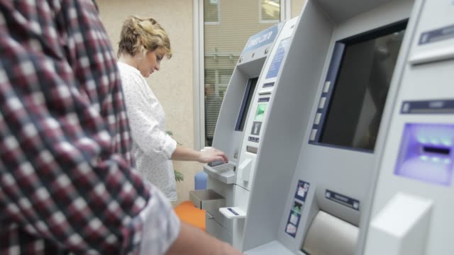 in front of atm, handheld shot - banca video stock e b–roll