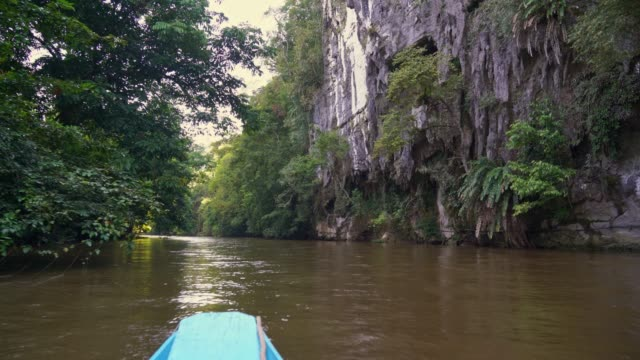 in front of clear water cave by boat close to deer cave, borneo islands - karst formation stock videos & royalty-free footage