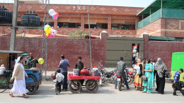 in front of saint mary's kids campus jesuit school street life balloon seller and parents picking up their kids from school - un giorno nella vita video stock e b–roll