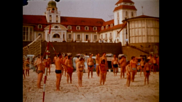In front of the famous Travel Charme Kurhaus in Binz on the island Rügen a group of tourists is doing early morning exercises as a woman coaches them...