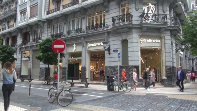 In Getaria Kalea pedestrianised street in San Sebastian With people passing and some pushing buggies/prams/transport systems Stradivarius is a...