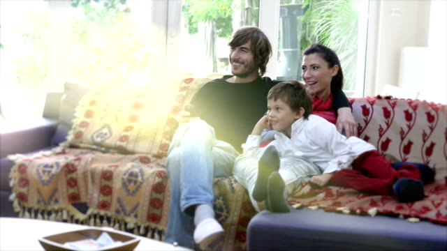 in holiday happy turkish family watching tv at home - listening stock videos & royalty-free footage