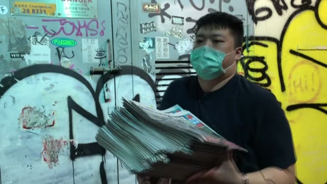 in hong kong's workingclass mong kok district people queue in the early hours at newspaper stalls to get the first copies of the apple daily a day... - routine stock-videos und b-roll-filmmaterial