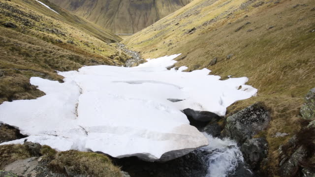In late March 2013, six inches of snow fell on a strong Easterly wind which blww the snow into massive drifts, accumulating on West facing slopes. Raise Beck above Dunmail Raise in the Lake District, UK, was filled in to a depth of 40 feet in places.