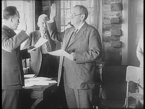In log cabin Harlan Stone raises hand and receives oath of office from Wayne Hackett / Stone shakes hand of a Hackett on completion / Stone shakes...