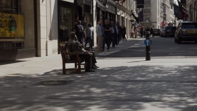 in mayfair london at the bottom of new bond street with people locals and tourists walking past it was intimacy that britishamerican sculptor... - two people stock videos & royalty-free footage