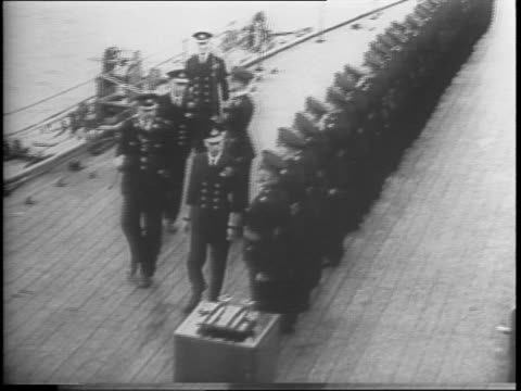 vídeos de stock e filmes b-roll de in north england, king george vi of england takes inventory of british naval fleet / fleet of ship in harbor / guns on front of warship / king george... - enfeites para a cabeça