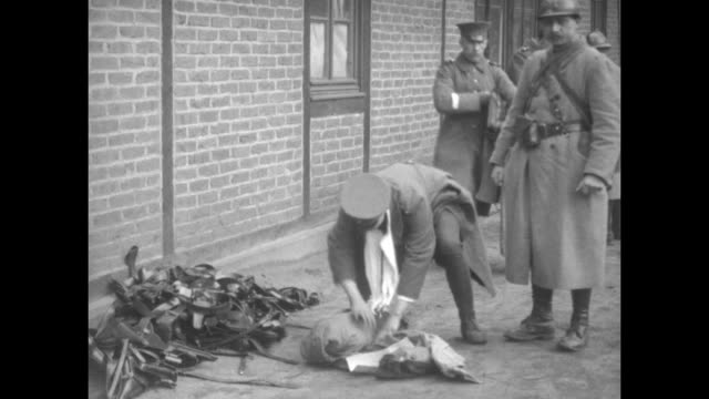 german police walking with bags and coats along road passing french soldiers / vs french soldiers searching german police and their belongings and... - erster weltkrieg stock-videos und b-roll-filmmaterial
