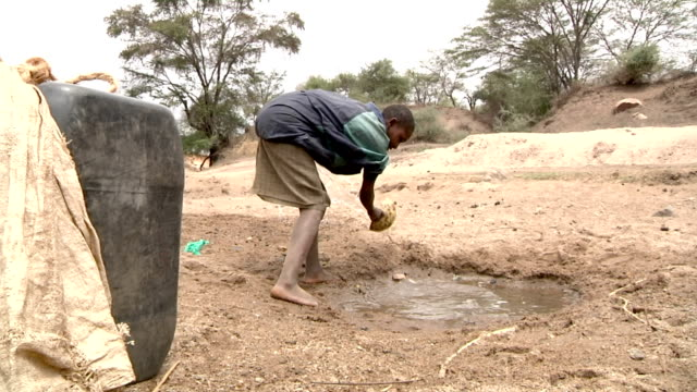 in order to get only clean water boy spilling dirty water out of small water well on july 29 2011 in road from garissa to dadaab kenya - dirty stock videos & royalty-free footage