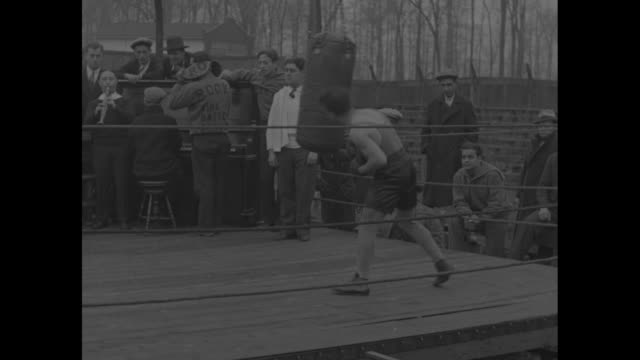 vidéos et rushes de in outdoor ring bushy graham jumps rope as small jazz band plays behind him ringside / men in overcoats and sweaters watch as he punches bag and band... - 1920 1929