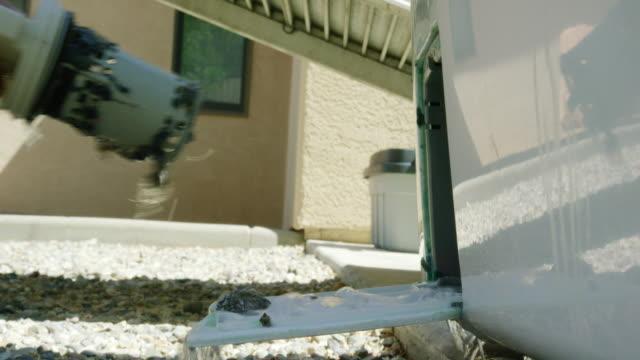 stockvideo's en b-roll-footage met ter voorbereiding op het verplaatsen, de handen van een blanke man schroef en laat de onderste pomp plug van een kleren wasmachine en giet water op naar grind buiten - wasmachine