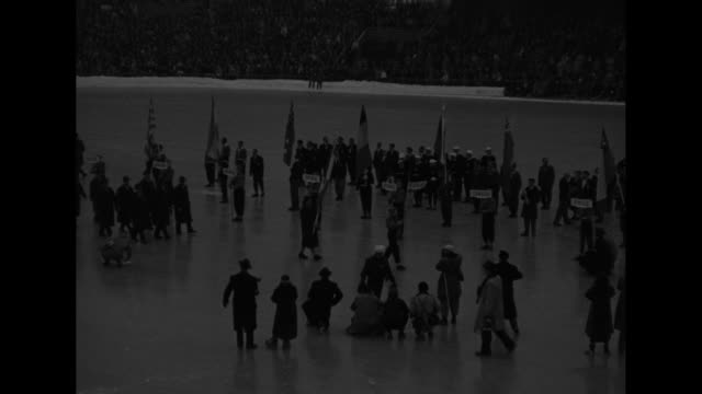 in procession for opening ceremonies participant holding usa sign walks across ice rink in bislett stadium in oslo / wider view of participant... - participant stock videos and b-roll footage