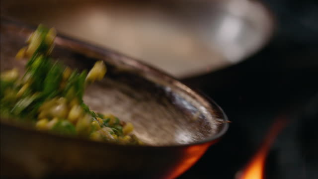 In restaurant kitchen, chef flips corn succotash in iron skillet over flaming stove in slow motion