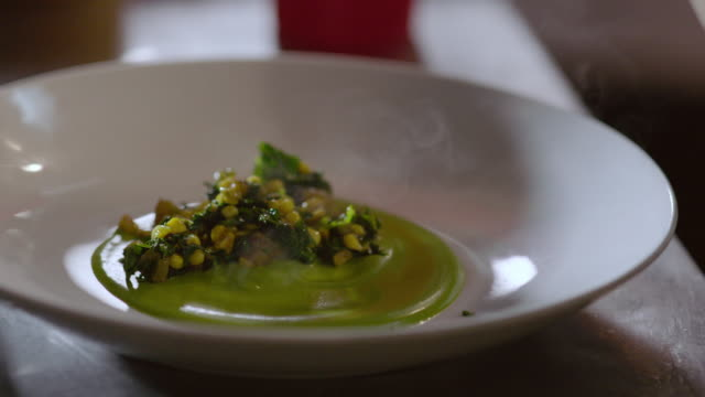 in restaurant kitchen, chef serves succotash from skillet onto dinner plate - feinschmecker essen stock-videos und b-roll-filmmaterial